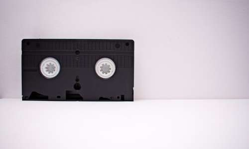 black-and-white-vhs-tape-on-white-wooden-surface-1302308